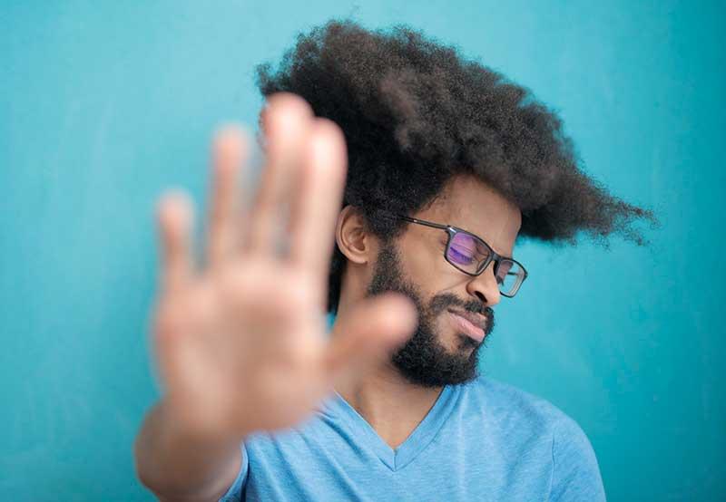 Hombre con la mano indicando un stop para las relaciones